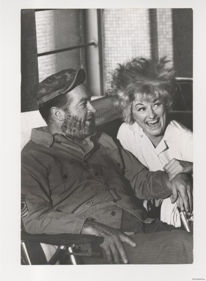 A black and white photograph of a seated man and woman. The man wears a hat and military-esque clothes. The woman wears a white top and leans into the man, laughing