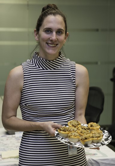 A woman in a sleeveless striped dress holds a plate of food in front of her. The black and white patterned plate has a number of cupcake-like treats that are orange and look to be topped with cheese.
