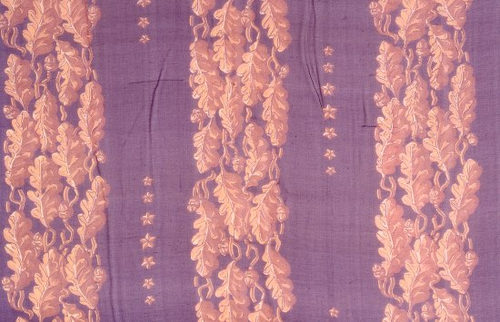 A close up view of the textile which is maroon in color with gold/bronze leaves and stars.