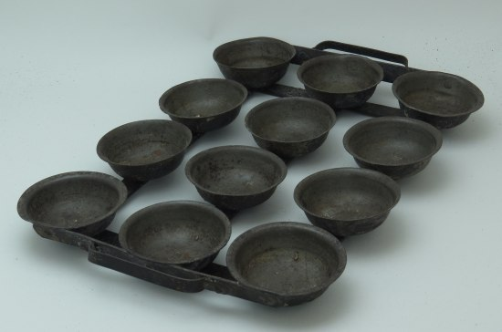Twelve black, small, bowl-like pans secured together for baking