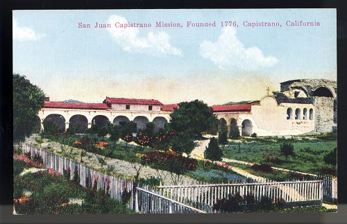 A photograph or illustration of a Mission from California in the 1770s. There is a fenced-in yeard that is full of growing things. The Mission building is in the back with a long colonnade and arches.