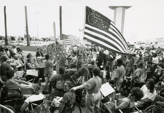 "Tightly packed group of people protesting near parking lot with palm trees visible. In center of photo, a US flag with person in wheelchair symbol instead of stars waves, help up by a woman. Protesters, many of whom are using wheel chairs, have signs saying ""No More Pity!"" and ""Freedom Now."" There are people with photo and video cameras at edges of group."