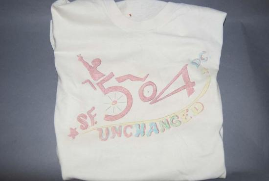 "The 504 occupation of a federal building galvanized people and created a strong sense of purpose and pride. Kitty Cone made this hand-drawn T-shirt of a person in a wheelchair and the words ""504 Unchanged, SF, DC"" while inside. The protests drew national attention and on April 28, 1977, the government finally released the regulations"