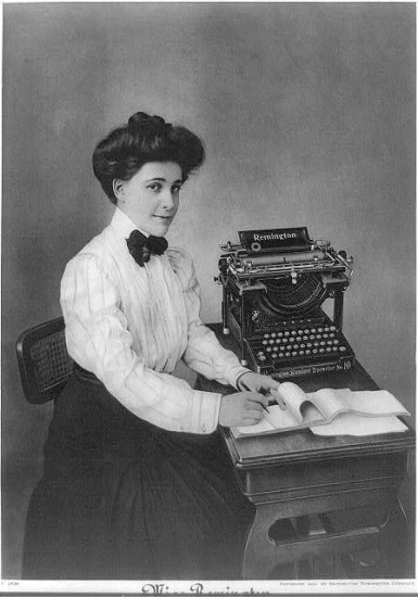 Black and white photograph of a woman sitting at a desk in front of a large typewriter