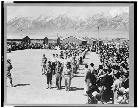 Black and white photo of gathering in center of camp with buildings in background. Boy Scouts line up while community watches. In background, high mountains with snow on top.