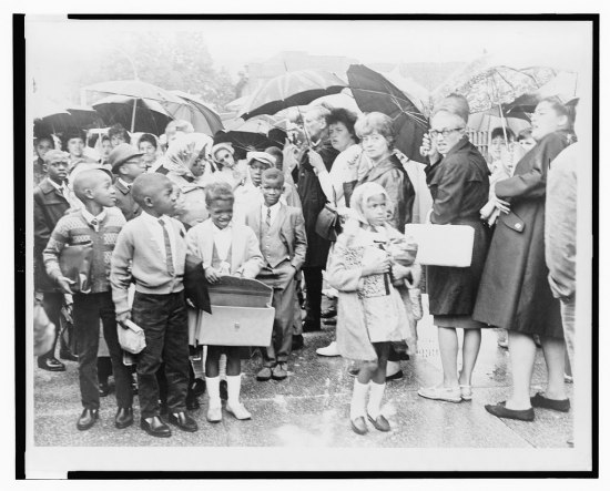 Photograph of a group of African American schoolchildren waiting in a group on the sidewalk in the rain. Next to them stand a line of white men and women holding umbrellas.