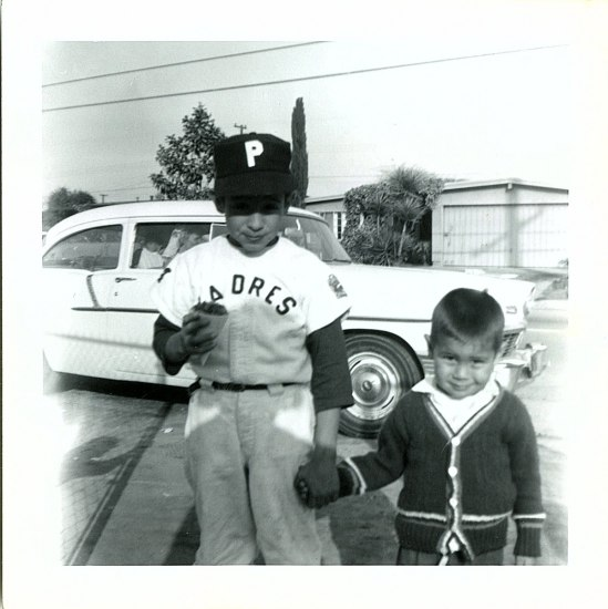 Ernie Martinez and Howard Martinez pose holding hands as children. Ernie is wearing a Padres baseball uniform and holding an ice-ream cone. A white car is in the background.