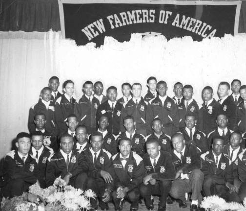 "A group of young African American men in black jackets, white collared shirts and ties kneels or stands under a sign that says ""New Farmers of America"""