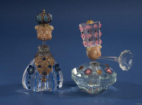 Two puppets with elaborate clowns and wide eyes, their bodies made of perfume bottles