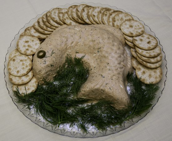 A salmon-colored food made from a mold that looks like a jumping fish sits next to crackers and a mass of dill on a clear serving tray. Its eye is represented by an olive slice.