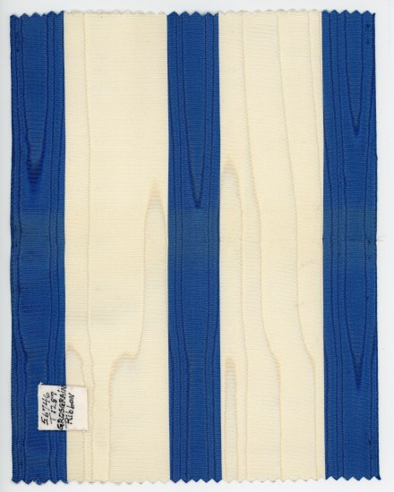 Piece of ribbon with blue and white vertical bands, which are wide.