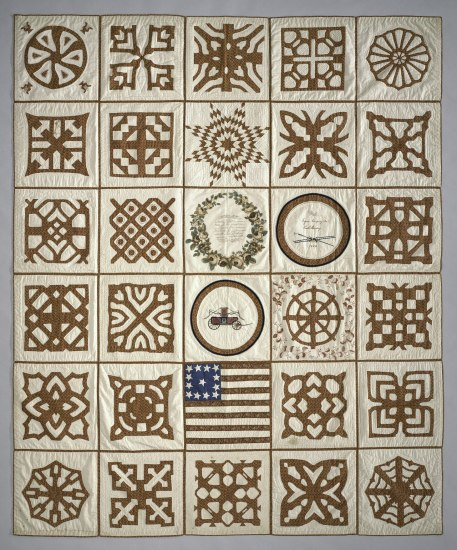 A cream-colored quilt with 30 squares outlined in brown. Each quilt square has a different geometric design, with three of the central squares depicting an American flag, a wheeled vehicle, and a wreath