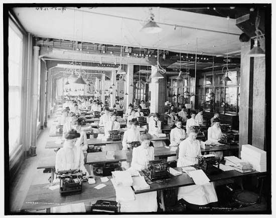 Black and white photograph of women sitting in close rows working on typewriters
