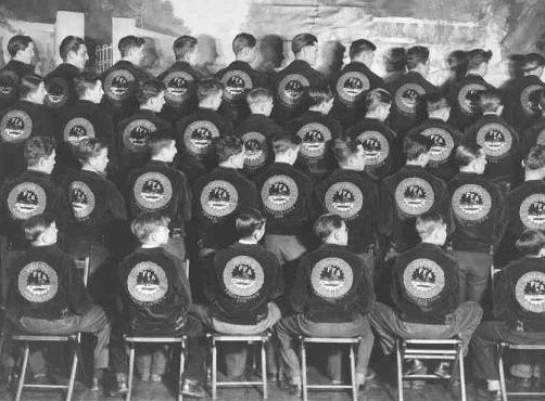 Young men sit in rows with their backs to the camera on backless folding chairs. They all look to the right as they wear black jackets with a large circular design on the back.