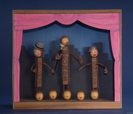 Three puppets made of chocolate bars standing on a stage with pink curtains