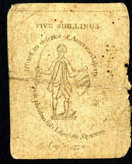 A piece of yellowed paper that says five shillings on it and has an illustration of a man in colonial garb holding a sword and a roll of parchment. There is other text on it.
