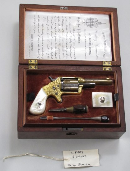 A pistol with a white handle in a wooden box with a letter written in cursive secured inside the lid