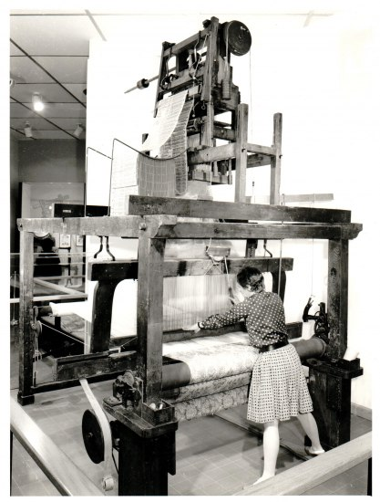 A woman stands facing a large loom made out of wood which is making jacquard textiles.