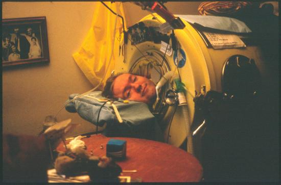 Color photo of young man in Iron Lung machine, his head on a blue pillow. Photos and stickers decorate the machine. Family photo hangs on wall behind him.