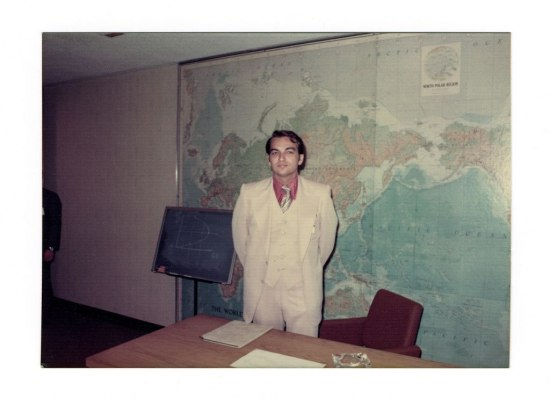 Jude Wanninski stands in a white three-piece suit and a pink shirt, in front of a map of the world. Behind him on a chalk board is a sketch of the Laffer curve.