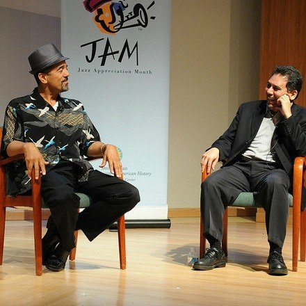 Two men talking on stage during Jazz Appreciation Month