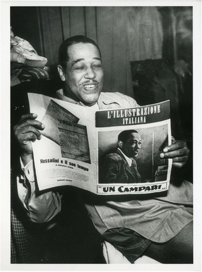Man smiling, reading a magazine