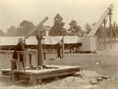 Sepia-toned photograph of an outdoor scene. There is a wooden platform on the grass. On it, a man sits at a desk-like table and peers into a large telescope that is pointed at the sky. He wears a hat. In the background, a tent-like structure is visible.
