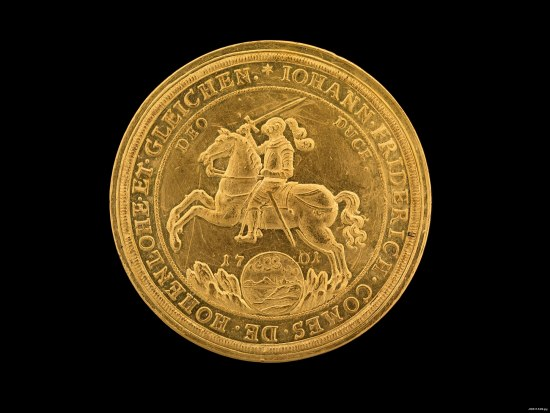 One side of a gold coin. There is a knight in armor on a horse with its legs reared. The man holds a sword and the horse is above splashing water and a globe-like detail. Text is around all of the outside of the coin.