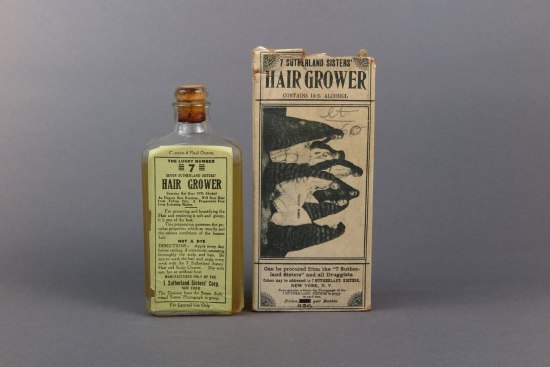 "Glass bottle labeled ""hair grower"" beside packaging featuring black and white image of seven women with long hair."