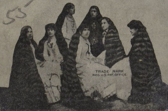 Black and white photo of seven women with exceedingly long hair.
