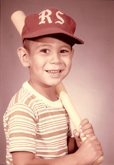 """Portrait photograph of a young Howard Martinez. Martinez poses wearing a baseball cap with the initials """"RS"""" and holds a baseball bat at the ready over his shoulder."""