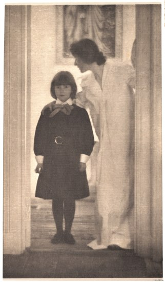 An old photograph. A young girl in a black dress stands in a doorway. A woman next to her turns her head back as she leans over, as if to whisper instructions or a secret. She wears a flowy white gown. The woman and girl appear to be down the hall from the photographer, but the shot is cropped.