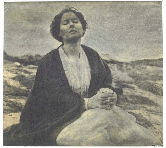 A photograph that is awash in tones of grey. A woman sits in a moor-like environment with a white dress and black shawl or robe. Her face is lifted up and her eyes are closed. Her hands are clasped together as if in prayer