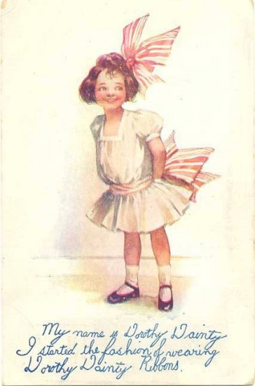 Postcard with an image of a smiling little girl wearing a white dress. She has a giant pink bow on her head and on her dress.