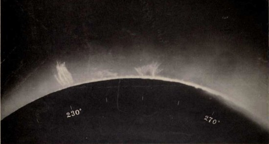 Photo during an eclipse. Black and white. Shows a part of a celestial body with a glow around it, including what appear to be two white flares.