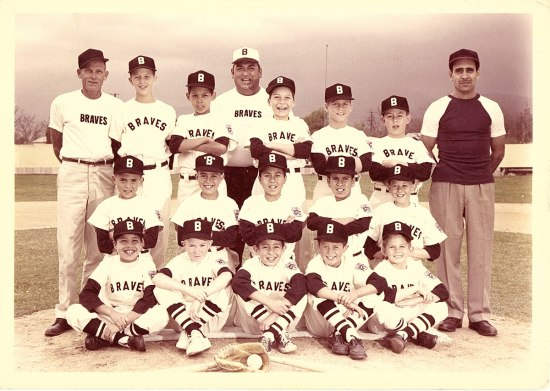 Team photograph of with coach Leopoldo Martinez and player Ernie Martinez. The Little League team, the Braves, pose on a baseball field in their uniforms. A glove and ball is posed in front of the group.