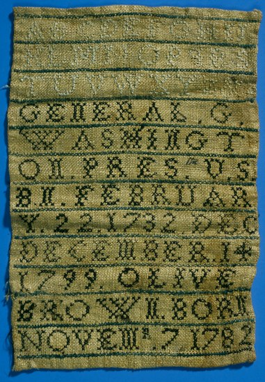 A brown sampler with black and white lettering