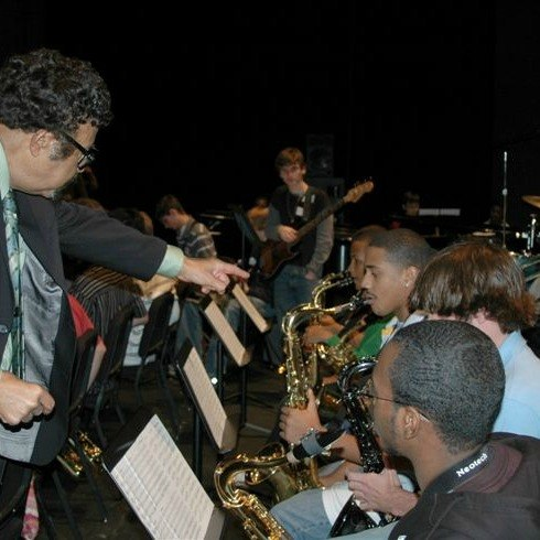 Conductor teaching saxophone students playing music