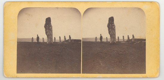 oblong stones ring a large standing stone in the middle of a field with a man next to it.