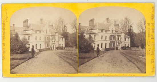 Photograph of a man in a top hat walking up the lane to a white house with three levels with trees surrounding