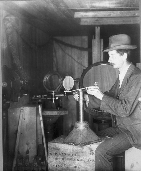 Black and white photo. A man wearing a hat sits in a small room manipulating a device of some sort.