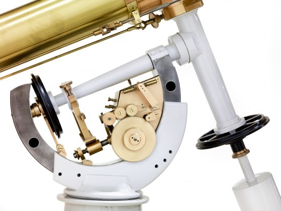 Photograph in color. Part of a telescope. One large gear-like wheel with teeth seems to adjoin three smaller gear-like wheels with teeth. There is a center bar and horseshoe-shaped brace or body.