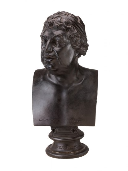 """A black plaster bust of George III depicts the king with an engaged expression, complete with open eyes and an open mouth. The bust's base is inscribed with the latin phrase """"pater patriae,"""" loosely translated as """"Father of the Country."""""""