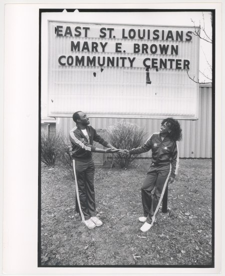 "In a black and white photo, Jackie Joyner-Kersee stands in front of a building with a large sign reading ""East St. Louisians Mary E. Brown Community Center."" She and her husband wear tracksuits and smile at each other as they grasp hands"