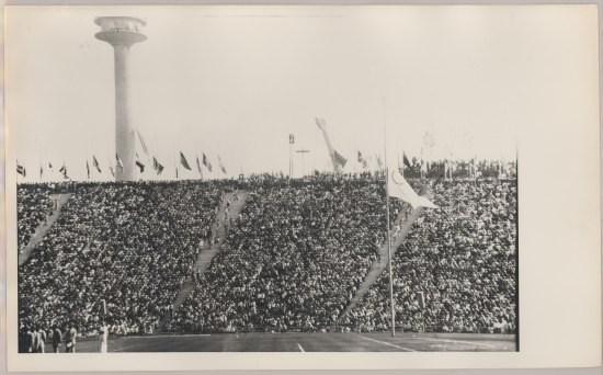 A black and white photograph of a crowded stadium with flags lining the top.
