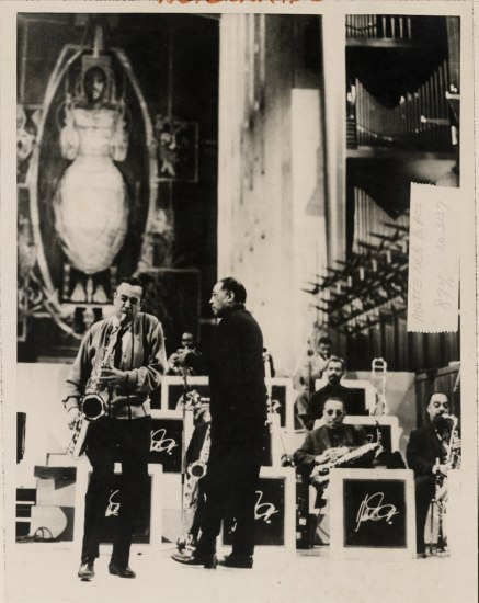 Black and white photo. In forefront, two men stand. Ellington holds microphone. Man plays saxophone. Behind them, musicians in bandstand, one wearing sunglasses. Behind that, it's clear that this space is a church. A stained glass window or mural depicts a saint or Jesus. And organ is visible.