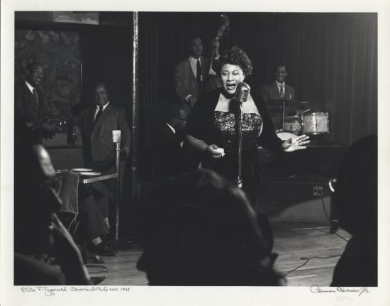 Black and white photo of woman on stage with microphone and sequined dress. Musicians behind her.