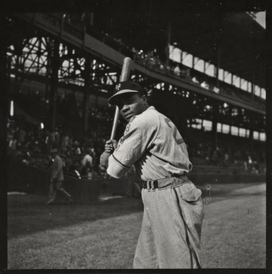 Photo of baseball player in uniform holding bat and looking at camera. In background, stands with seating with spectators.