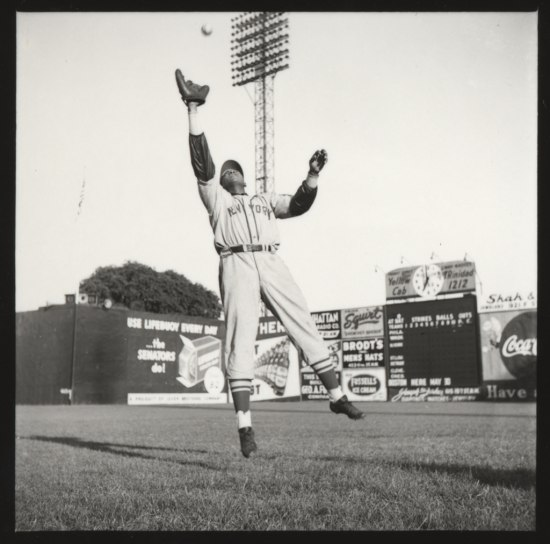 Black and white photo of a baseball player in uniform wearing a glove leaping into the air to catch a ball above his head, arm outstretched. Baseball field and Coca Cola ad in background.