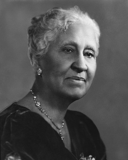 Black and white photographic portrait of a woman with very fancy earrings and necklace.
